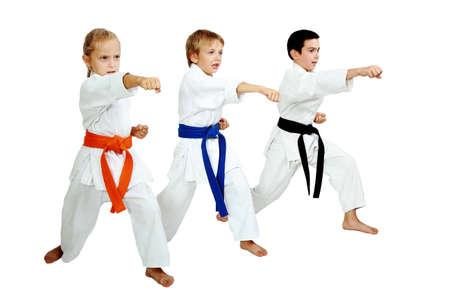 Drei Karateka im Kimono traf ein Schlag Arm