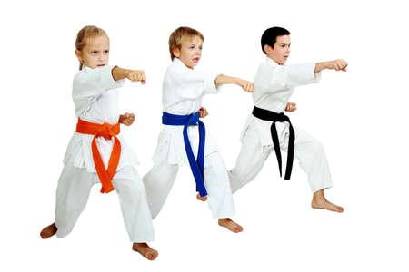 Three karateka in kimono hit a punch arm