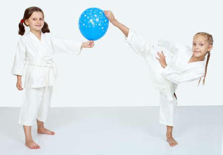 Zwei kleine Mädchen mit blauen Ball schlagen ein Karate-Kick Bein