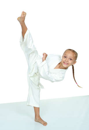 A little girl in a white kimono beat punch leg