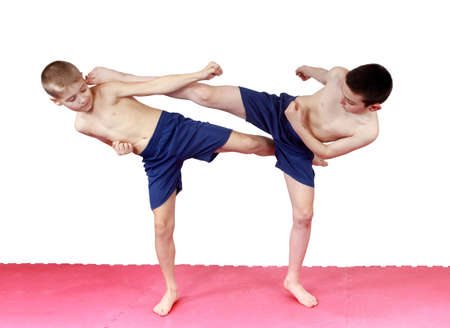krav maga: On the mat the boys perform blows legs Stock Photo