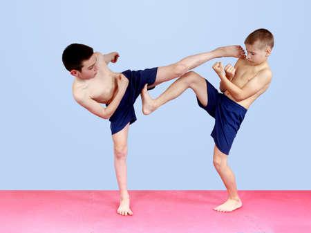 Jungen in kurzen Hosen sind zu schlagen Schläge Tritte