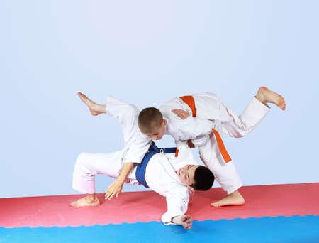 threw: Sportsman with an orange belt threw athlete with a blue belt