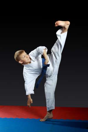 Left foot yoko-geri boy beat in the white karategi  photo