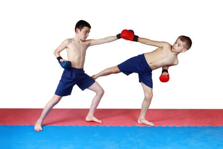 krav maga: Two athletes are training in shorts kick low kick on the mat
