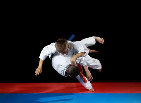 Zwei junge Athleten in den starken Rückgang führen Judowurf