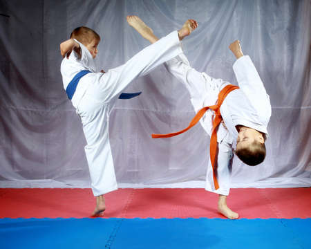 Blows legs to meet each other are beating athletes in karategi