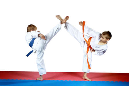 High kicks legs two athletes are training on the red and blue mat photo