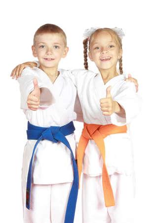 sport kids: Very happy boy and girl athletes in karategi