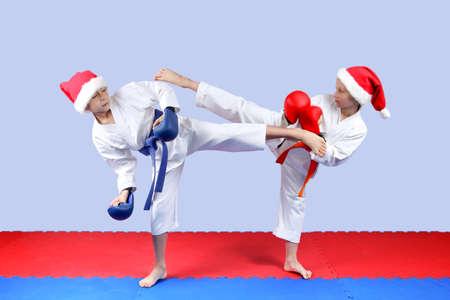 Mädchen und Junge in einer Kappe von Santa Claus sind schlag Bein bläst Karate