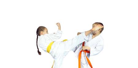 Little girl athlete in karategi  is beating to athlete leg on the head