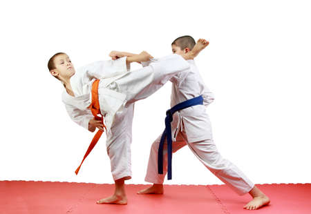 On a red mats sportsmen are training paired exercises karate