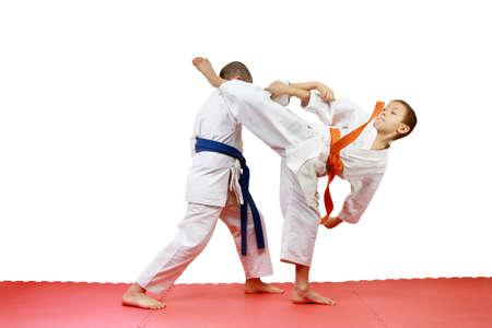 jiu jitsu: Young sportsmen in karategi are doing paired exercises