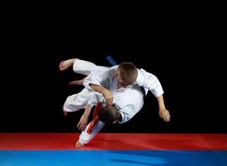 Young athletes in the sharp drop perform judo throw Фото со стока