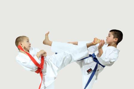 jiu jitsu: Two boys in karategi are beating blows kicks