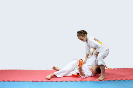 On the red and blue mat boy and girl in karategi are training throwing Stock Photo
