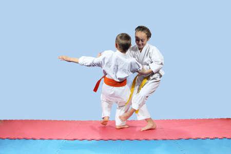 jiu jitsu: Girl with yellow belt makes slicing down under leg Stock Photo