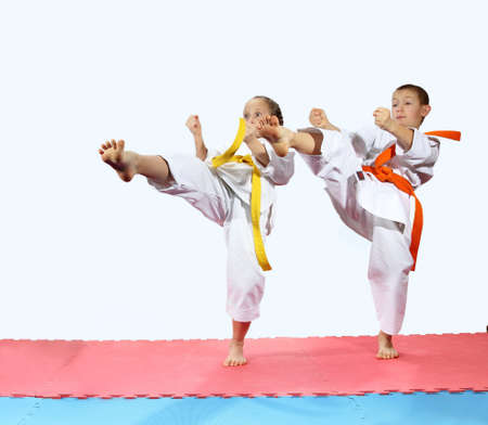 jiu jitsu: Girl and boy in karategi are beating kick leg forward Stock Photo