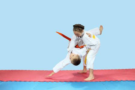Kleines Mädchen rollt Jungen auf den Matten Lizenzfreie Bilder