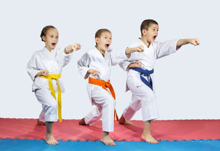arts: Two boys and a girl in karategi are hitting punch hand forward