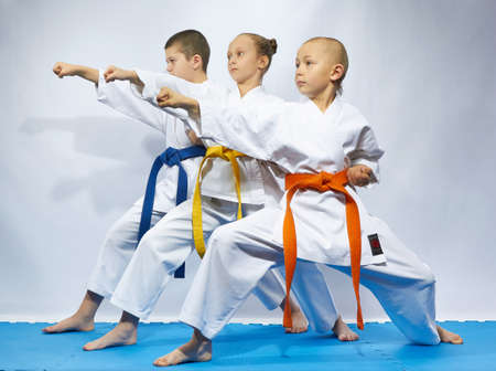Two boys and a girl in karategi are hitting punch arm