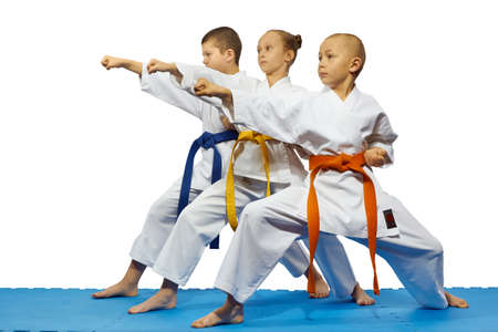 Young children athletes are beating kick gyaku tsuki on a white background