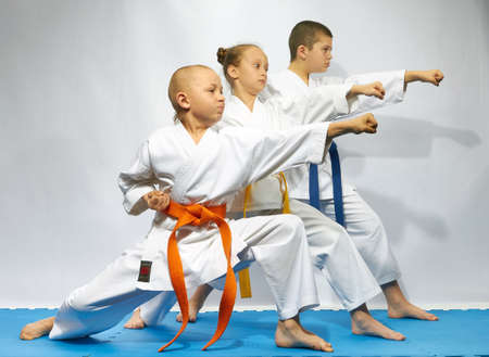 Straight punch arm are performing sportsmens on a blue mats Фото со стока