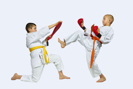 thai arts: The sportsman with the orange belt beats kick on simulator in the hands of another athlete Stock Photo