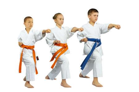 Zwei Jungen und ein Mädchen schlagen Kick gyaku-tsuki Lizenzfreie Bilder
