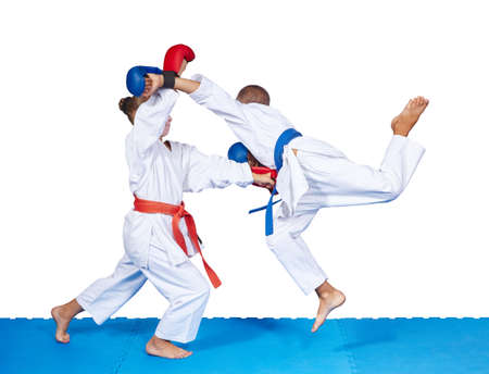 arts: Children are beating karate punches on the mat isolated