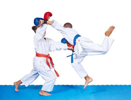 arte marcial: Los ni�os est�n golpeando golpes de karate en el tapete aislado