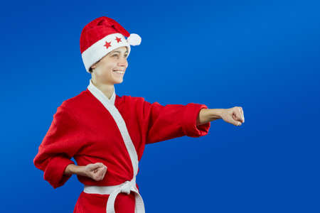 arts: girl in dressed as Santa Claus beats punch hand