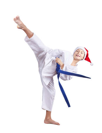 arts: Boy in a cap of Santa Claus beats a high kick leg Stock Photo