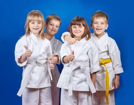 Children in karategi are showing finger super Фото со стока