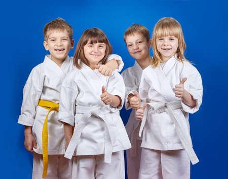 Four cheerful sportsman in karategi are showing finger super Imagens