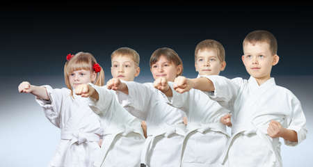Five little athletes hit a punch on a gradient background Stock Photo