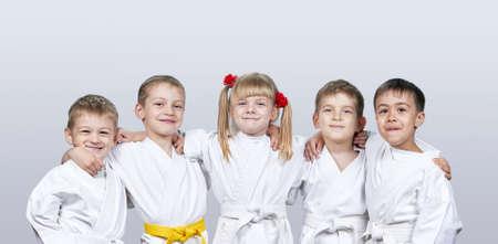 Fröhliche Kinder in karategi auf einem grauen Hintergrund