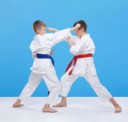 paciencia: Chicos están entrenando golpes de karate y bloques sobre un fondo azul Foto de archivo