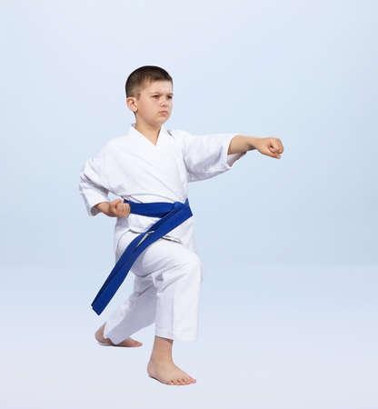 Boy in karategi beats punch arm on a light background
