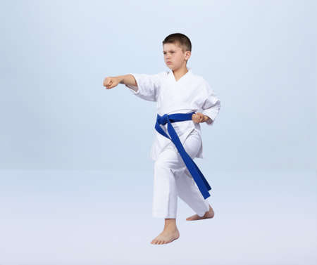 On a light background karate boy beats punch arm Stock Photo