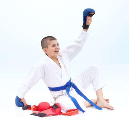 left hand: Boy athlete raised his left hand to greet