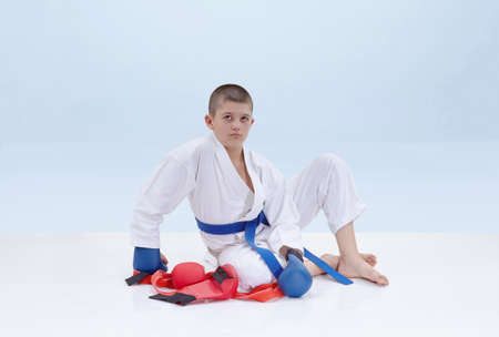 Karate boy in karategi raised his hand in greeting stock photo 62958164 on a light background karate athlete sits near a karate outfit m4hsunfo