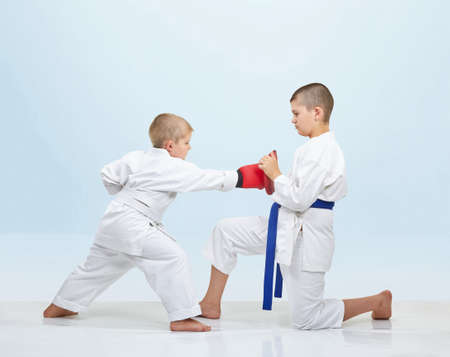 Boy karateka beats punch on fitness machine that brother keeps Stock Photo