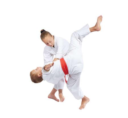 Children make the throws of judo in judogi