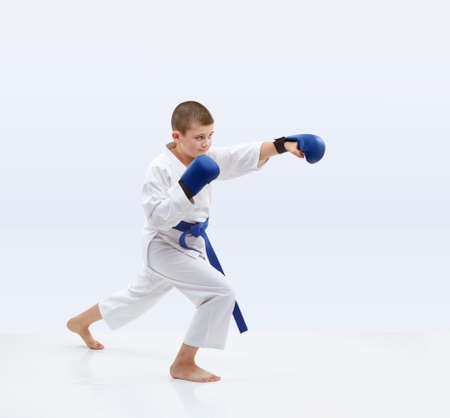 On a light background karateka with blue overlays on hands is beating punch Stock Photo