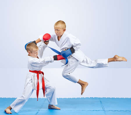 overlays: Two karateka with overlays on the hands are training punch in jump and block