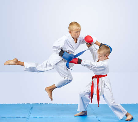 With the blue overlays on the hands athlete hits a punch in the jump Stock Photo