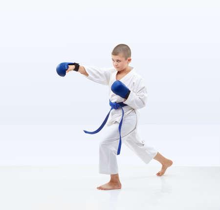 Boy beats a punch arm on a light background