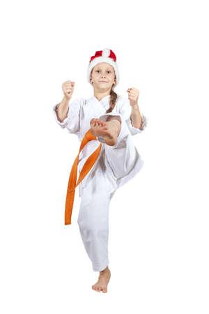Girl in the cap of Santa Claus hits a kick leg Stock Photo