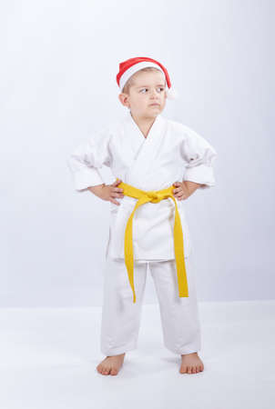 Karateka with a yellow belt and in cap of Santa Claus